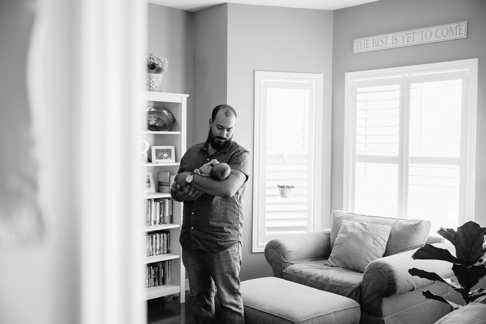 new dad standing in living room holding 2 week old baby son - Markham In-Home Photography