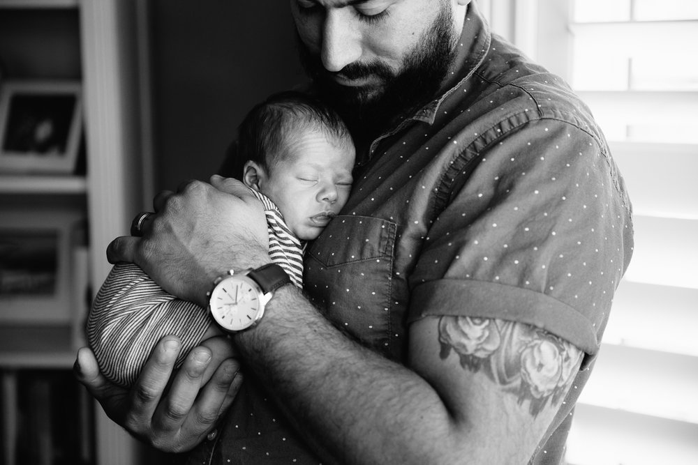 new father standing, snuggling sleeping 2 week old baby boy to his chest - Barrie In-Home Photography
