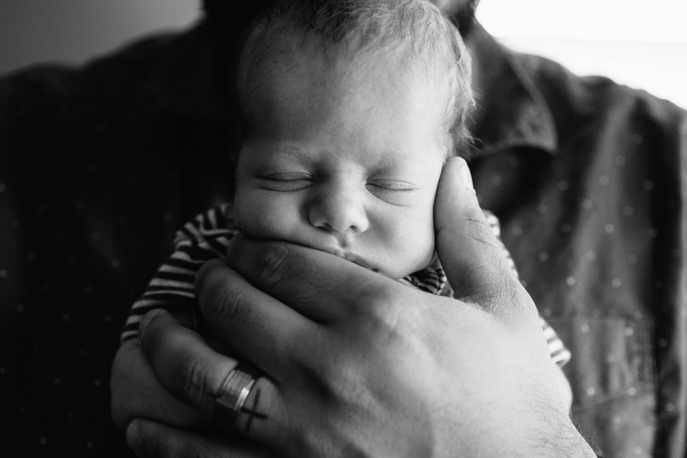 2 week old baby boy sleeping with chin resting in father's hand - Newmarket Lifestyle Photos