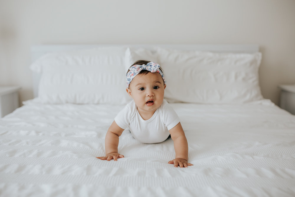 6 month old baby girl with floral headband on crawling on white bed, looking at camera -  Newmarket Lifestyle Photography