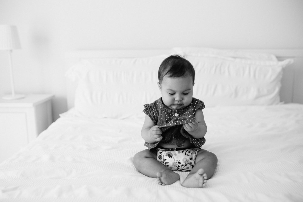 6 month old baby girl with dark hair sits on bed holding and looking at dress - Newmarket Lifestyle Photography