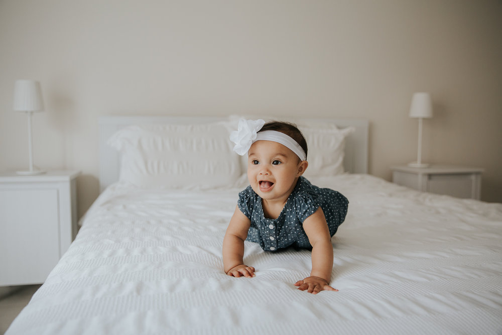 6 month old baby girl with dark hair and eyes in polka dot dress and headband crawling on bed, smiling -  Newmarket In-Home Photography