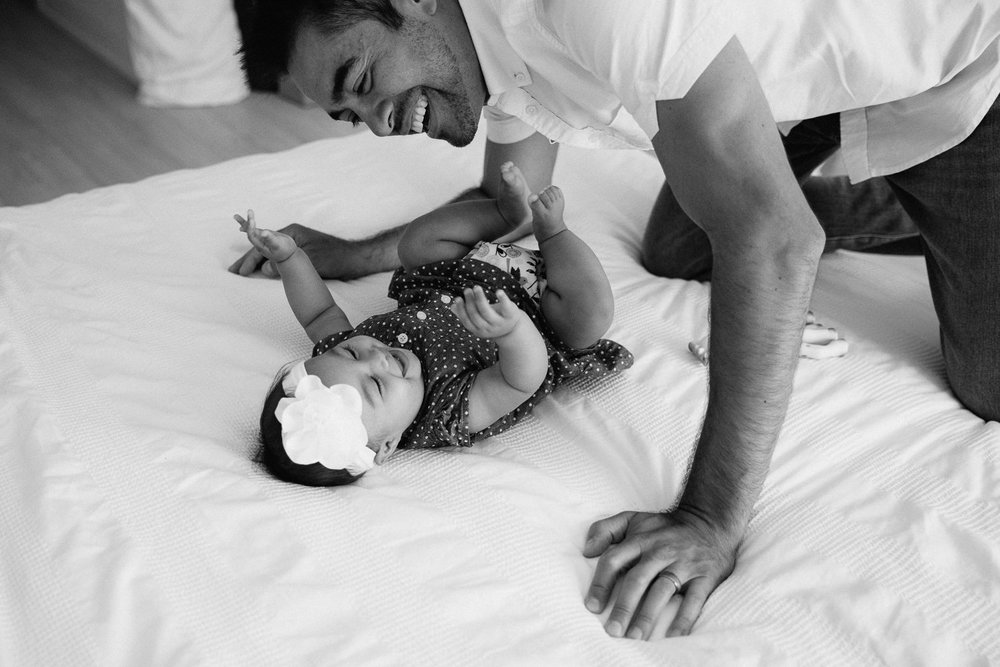 6 month old baby girl lying on bed laughing as dad leans over, tickling her - Barrie In-Home Photos