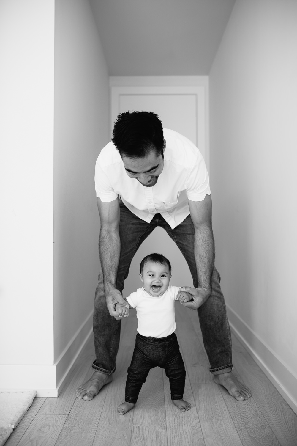6 month old baby girl walking and laughing, holding onto dad's hands - Barrie Lifestyle Photos