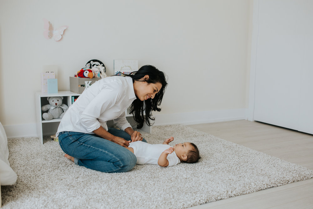 mom changing 6 month old baby daughter's diaper on nursery floor - Newmarket In-Home Photography