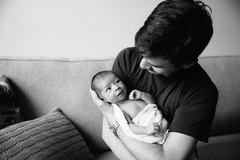 new dad holding 2 week old swaddled baby girl who is giving dad a funny look - Stouffville In-Home Photography