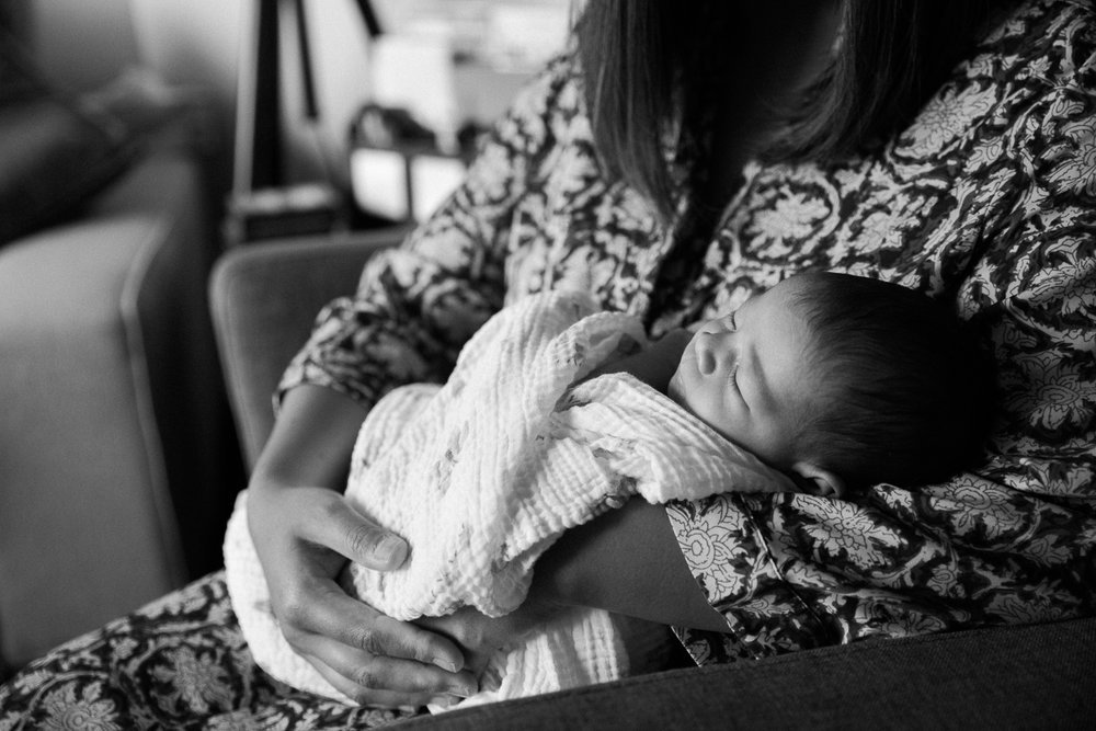 first time mother sitting on chair holding sleeping 2 week old baby girl - Markham Lifestyle Photography