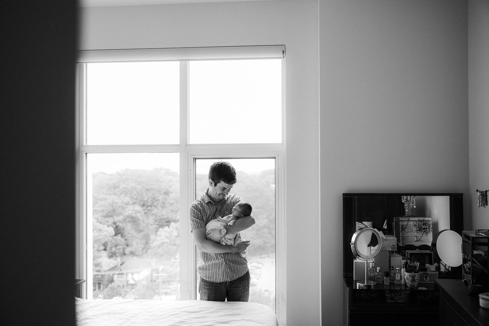 new father standing in front of window holding sleeping 2 week old baby daughter - Stouffville In-Home Photos