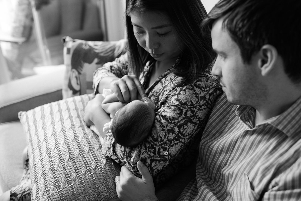 first time parents sitting on couch holding sleeping 2 week old baby girl - Newmarket Lifestyle Photos