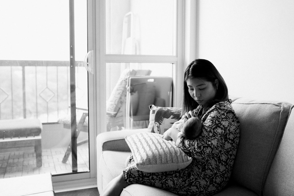 new mother sitting on couch holding sleeping 2 week old baby girl - Newmarket Lifestyle Photography