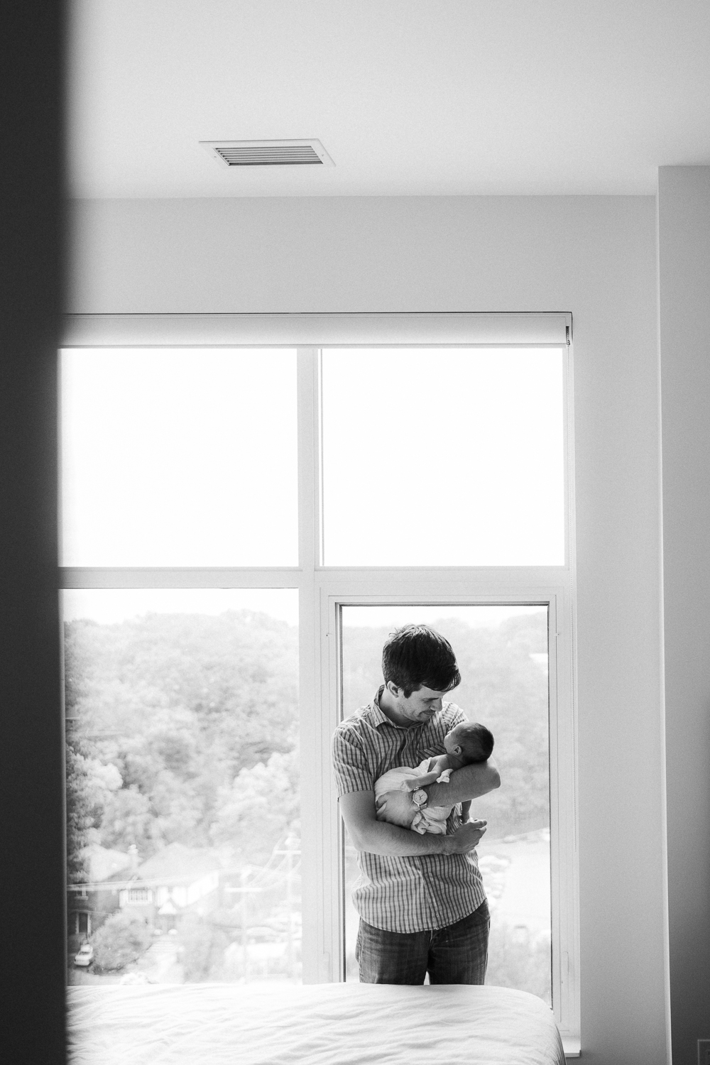 new father standing in front of window holding swaddled 2 week old baby girl - Barrie In-Home Photography