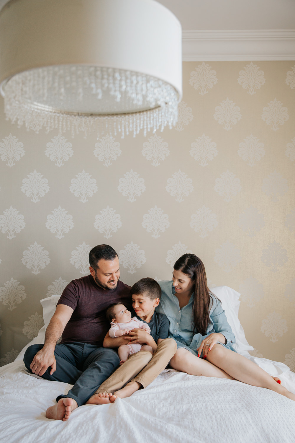 family of four sitting on bed, 9 year old boy holding 2 month old baby sister in pink onesie as mom and dad snuggled next to them - Barrie Lifestyle Photography