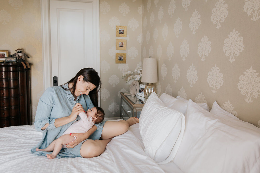 first time mother with long brunette hair in blue chambray dress sitting on master bed, smiling at 2 month old baby girl in her arms and holding her hand - Newmarket In-Home Photos