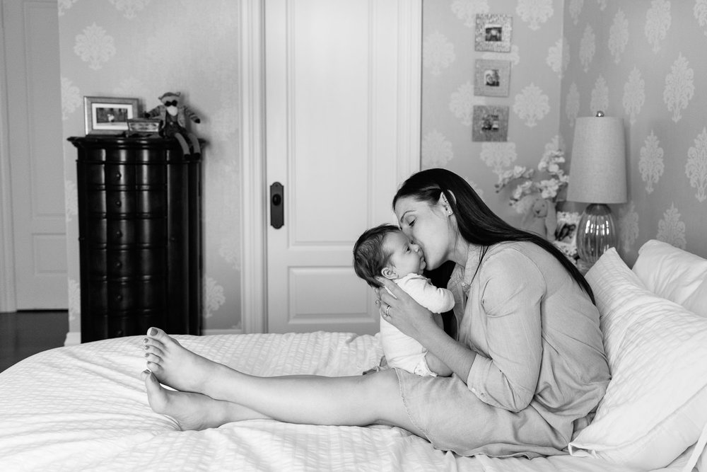 first time mother with long brunette hair in blue chambray dress sitting on master bed, kissing 2 month old baby girl on the cheek - Stouffville In-Home Photos