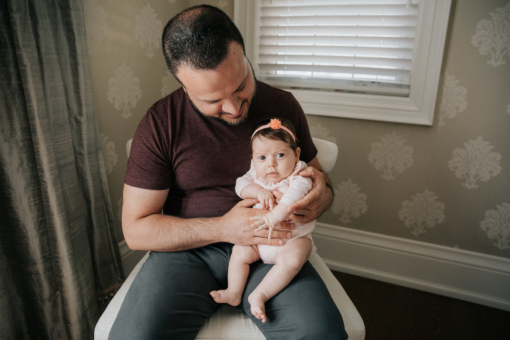 new dad in jeans and t shirt sitting in chair holding and smiling at 2 month old baby girl in pink onesie who is sitting on his knee looking at the camera - Barrie In-Home Photos