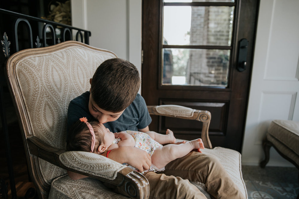 9 year old big brother sitting in chair holding 2 month old baby sister and kissing her on the forehead - Newmarket Lifestyle Photos