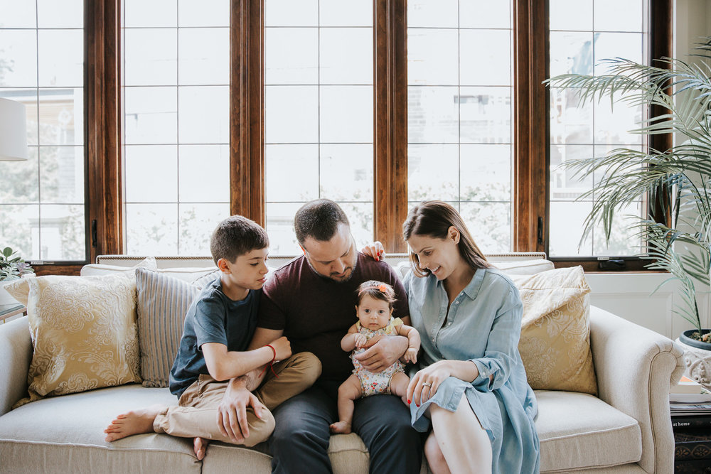 family of four sitting on couch, mom, dad and 9 year old son looking at 2 month old baby daughter in father's lap - Stouffville Lifestyle Photos