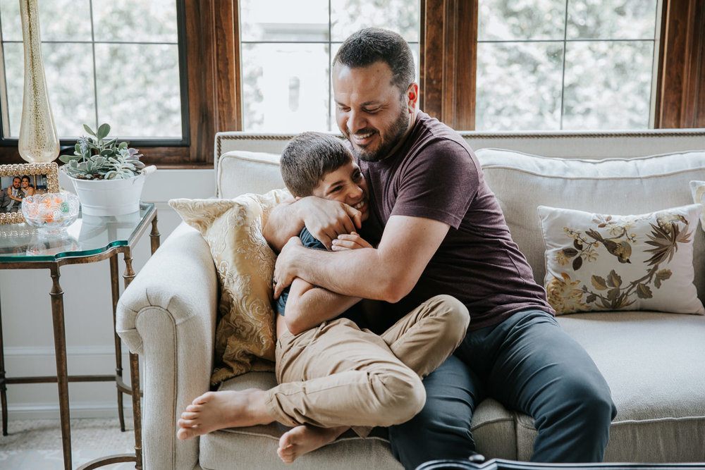 father hugs and tickles 9 year old son on couch, boy laughs - Stouffville Lifestyle Photography