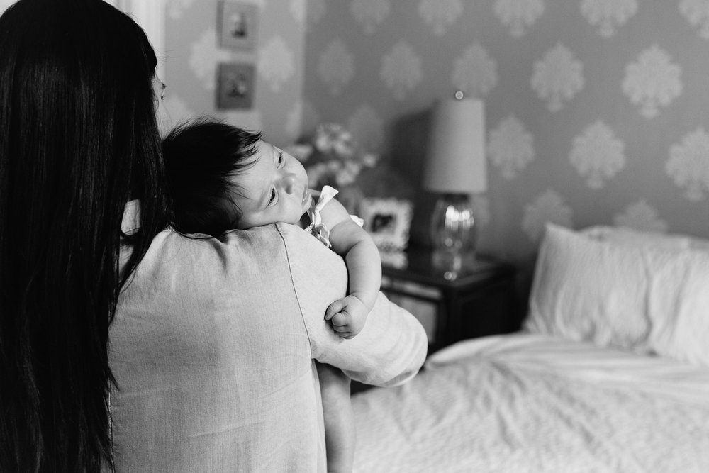 2 month old baby girl with lots of dark hair lying over mom's shoulder, waking up - Newmarket In-Home Photography