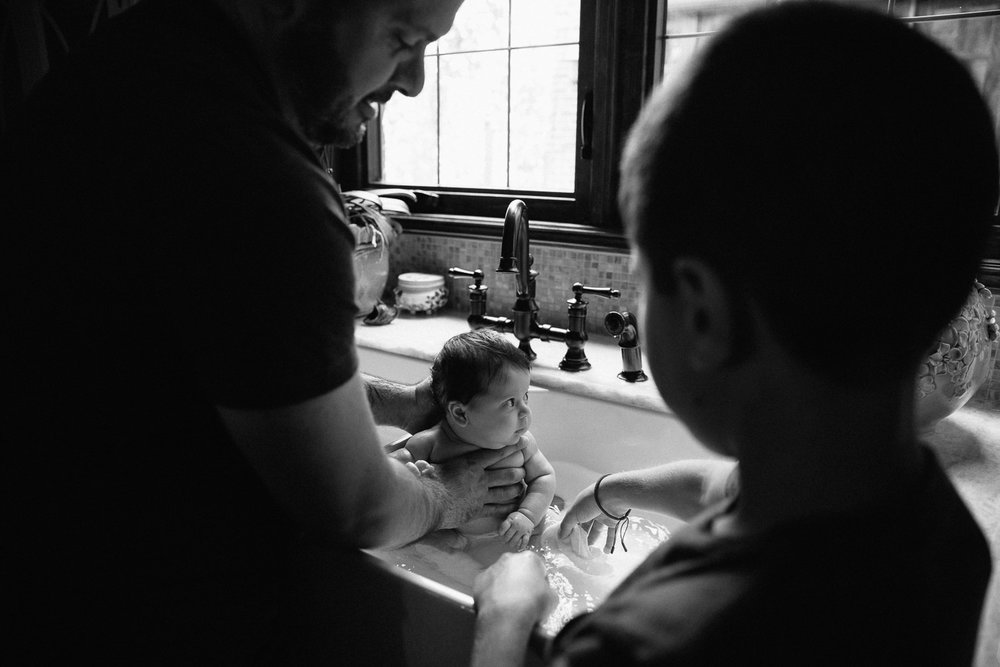 2 month old baby girl with lots of dark brown hair in kitchen sink getting a bath from dad and 9 year old big brother - Stouffville In-Home Photography