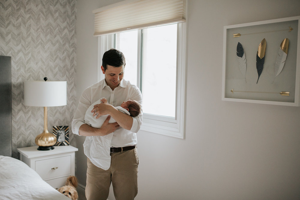 new dad standing next to bed in master bedroom holding 2 week old baby boy in white swaddle, rocking him to sleep - GTA Lifestyle Photography