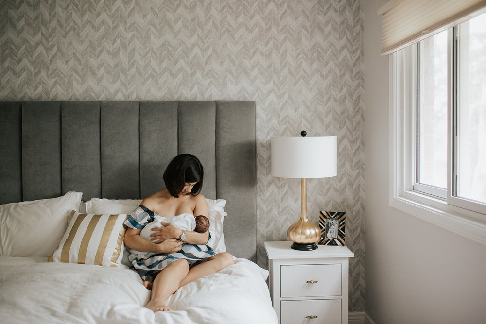 new mom with short brunette hair sitting on master bed nursing 2 week old baby boy in white swaddle - Markham In-Home Photography