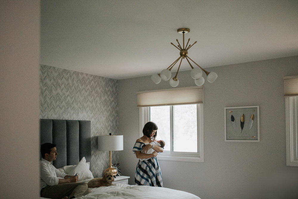 new mother standing next to bedroom window holding 2 week old baby boy in white swaddle, dad and dog sitting on bed - GTA In-Home Photos