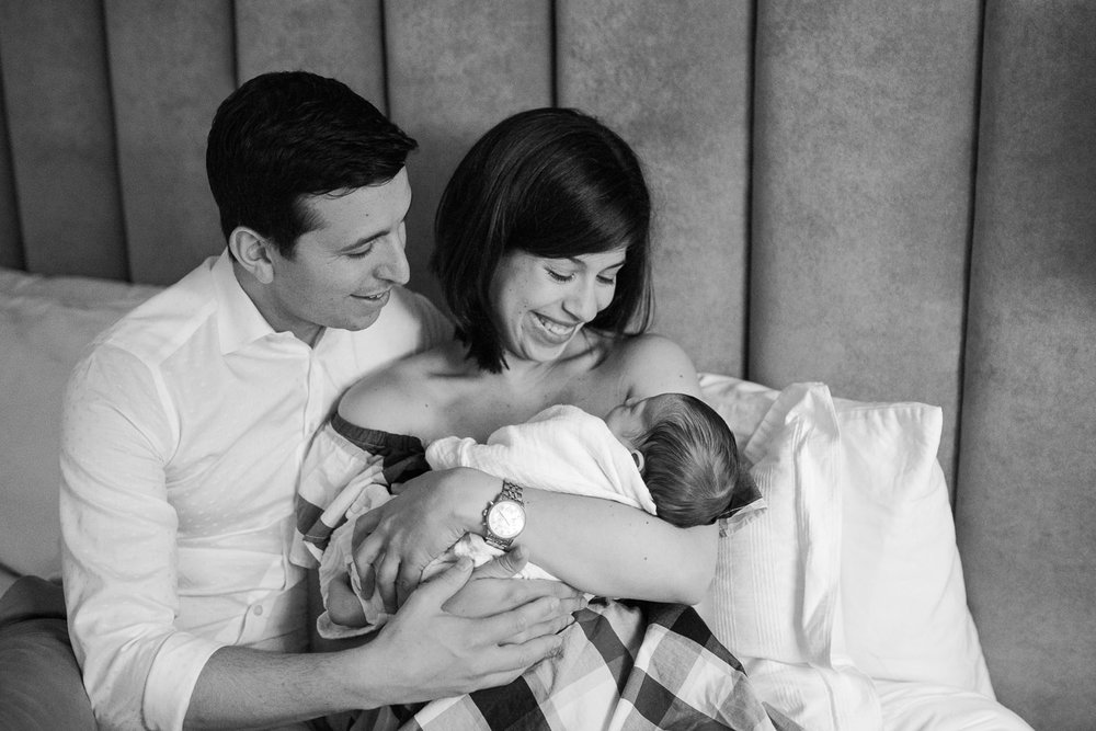 new parents smiling sitting on master bed, mom holding 2 week old baby boy in white swaddle and dad embracing them - Barrie Lifestyle Photos