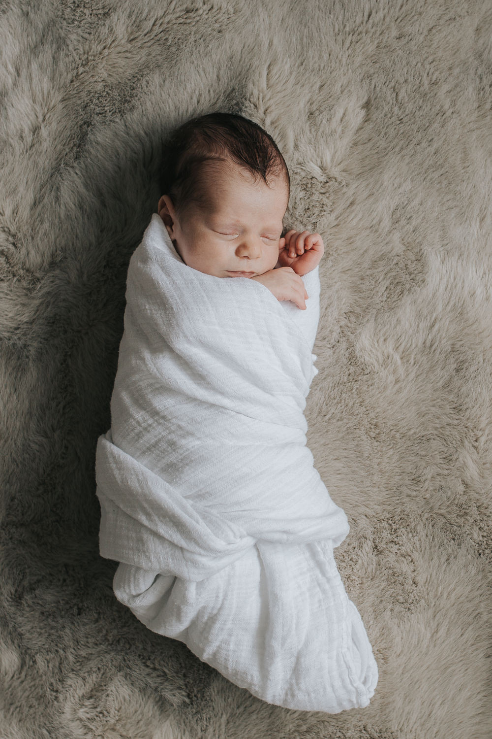 2 week old baby boy with dark hair lying on fur blanket in white swaddle, sleeping with hands next to face - Markham Lifestyle Photography