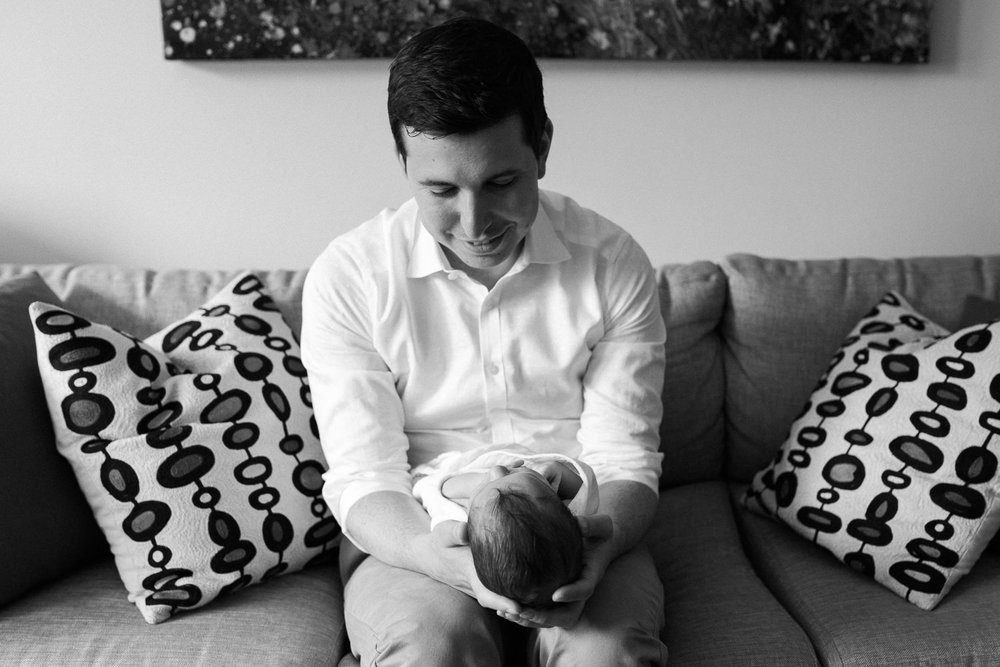 new father sitting on couch holding 2 week old baby boy in white swaddle, son's head resting in dad's hands - Barrie In-Home Photos