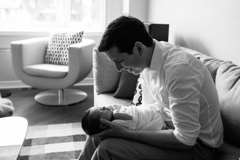 new father sitting on couch holding 2 week old baby boy in white swaddle, son's head resting in dad's hands - Newmarket Lifestyle Photos