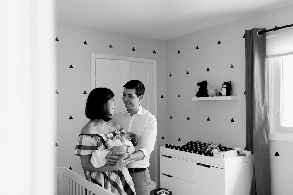 new parents standing in nursery, mom holding swaddled 2 week old baby boy with dark hair, dad looking at mom -  Newmarket In-Home Photography