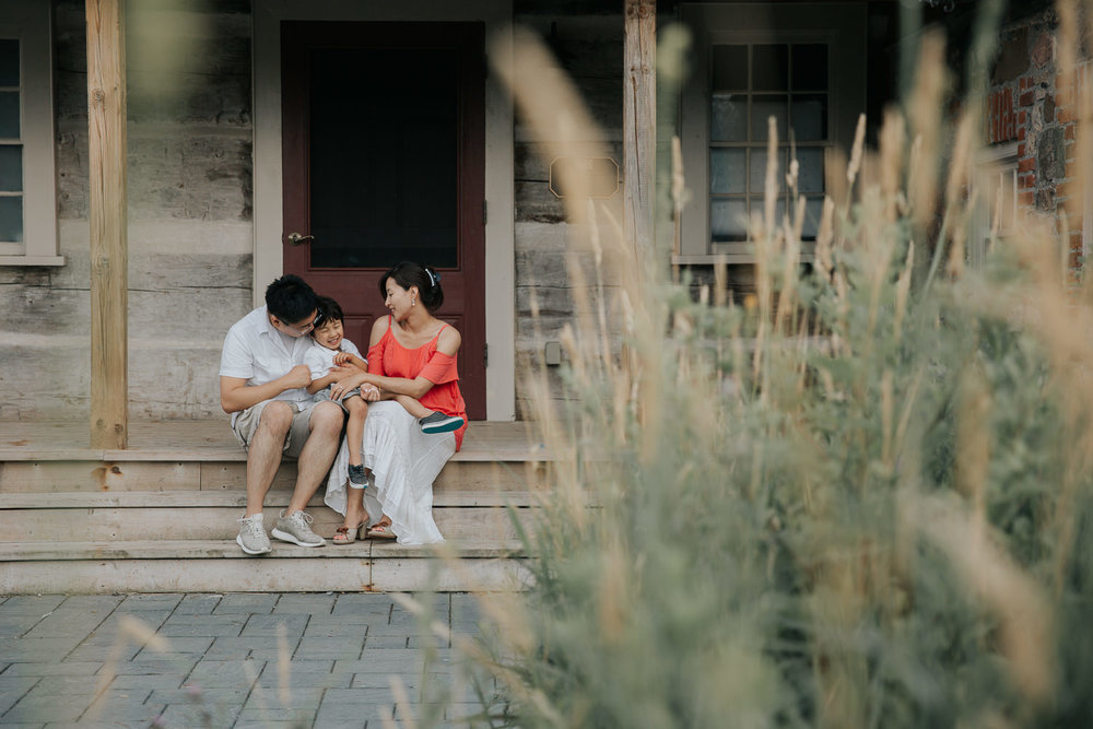 family of 3 sitting on front porch, toddler son sitting on dad's lap, laughing as mom tickles him, father and son in white shirts, mother wearing coral top - Markham Lifestyle Photography