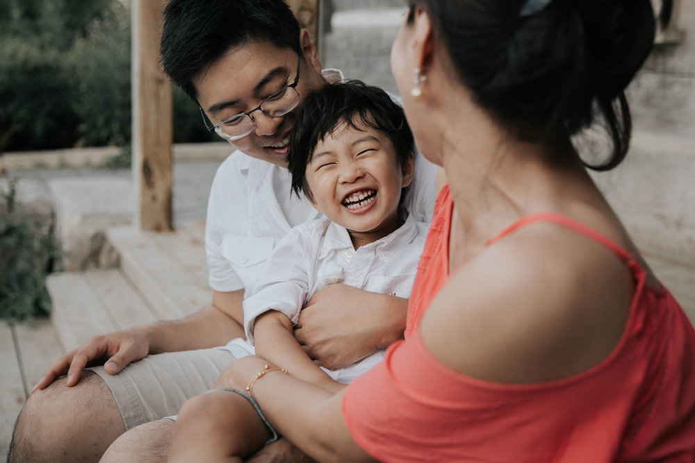 family of 3 sitting on front porch, toddler son sitting on dad's lap, laughing as mom tickles him, father and son in white shirts, mother wearing coral top - Markham In-Home Photography