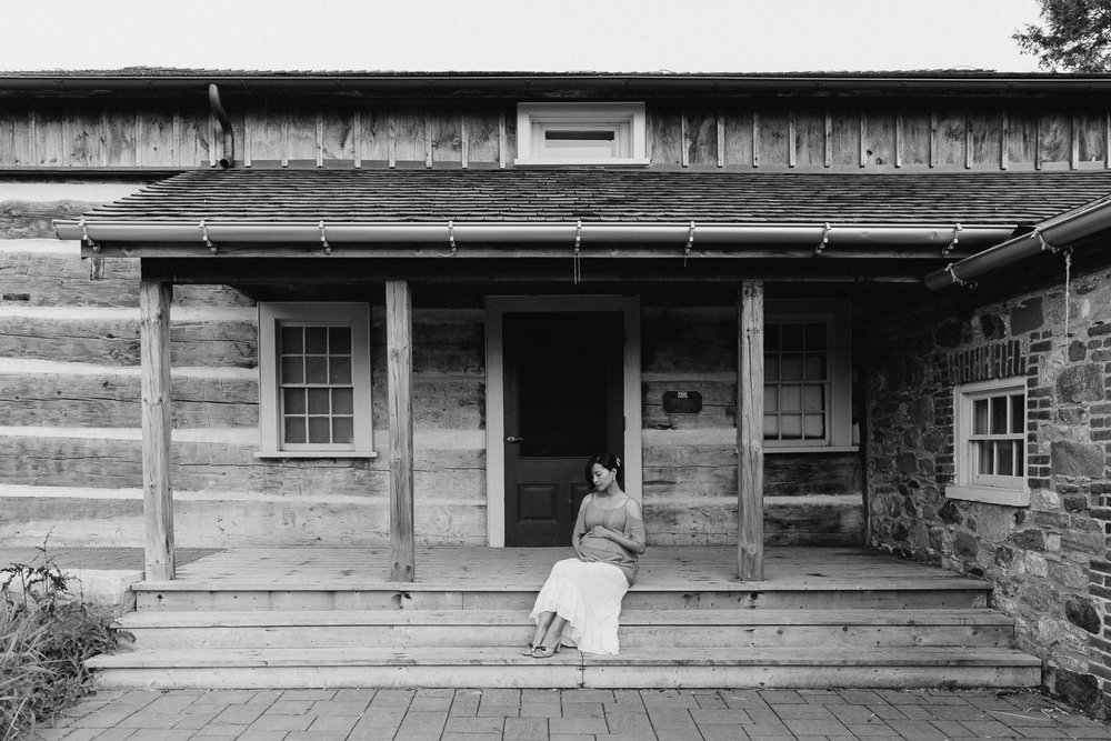 pregnant woman in flowing top and skirt sitting on porch in front of historic log home, holding baby bump - Barrie In-Home Photography