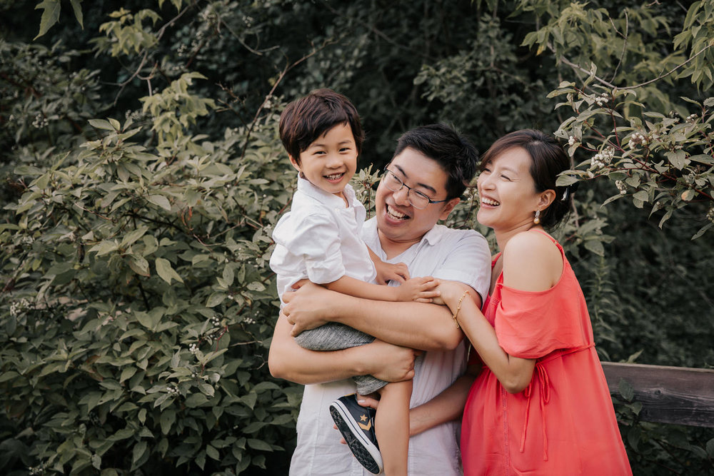 family of 3, father holding three year old toddler son who is looking at camera smiling, mom and dad looking at boy and laughing - Newmarket Lifestyle Photos