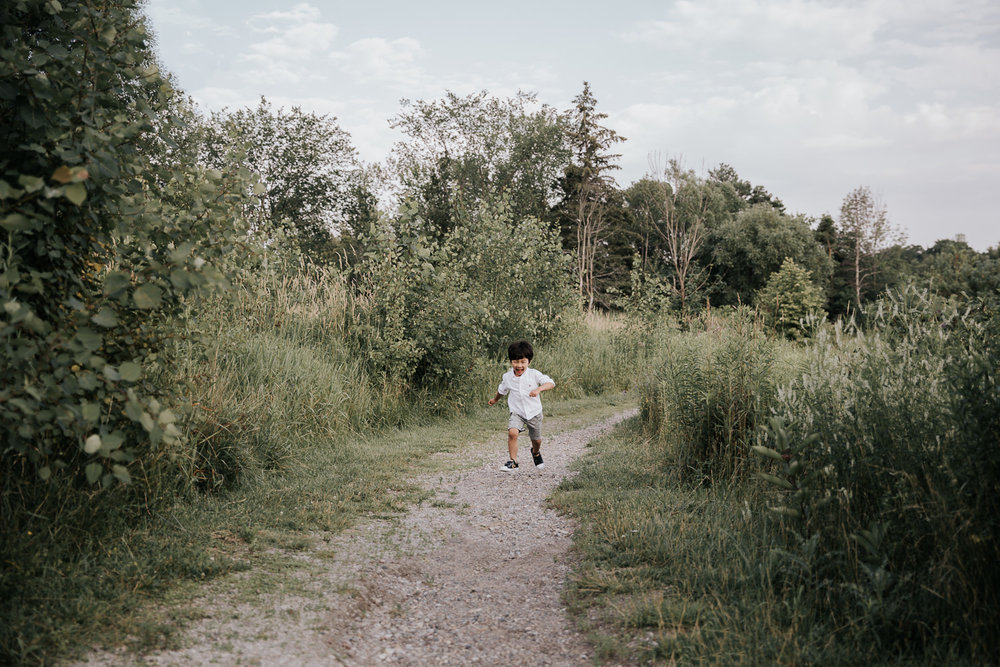 3 year old boy with dark hair wearing white shirt and grey shorts running down outdoor path smiling and full of joy -  Markham Lifestyle Photography