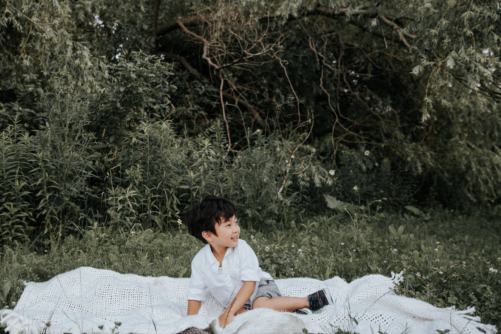 3 year old toddler boy with dark hair wearing white button down top and grey shorts sitting on white blanket in front of greenery and smiling and looking to the side - Barrie In-Home Photos