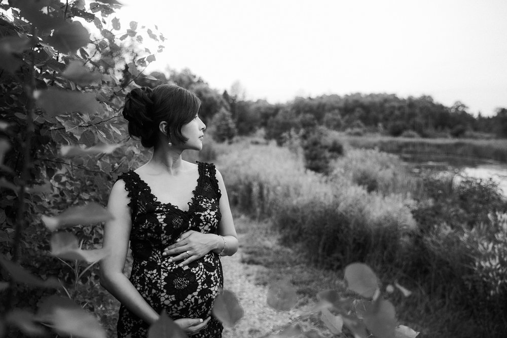 7 month pregnant woman with dark hair wearing black lace dress standing next to foliage, holding baby bump and looking off the the side - Stouffville Lifestyle Photography