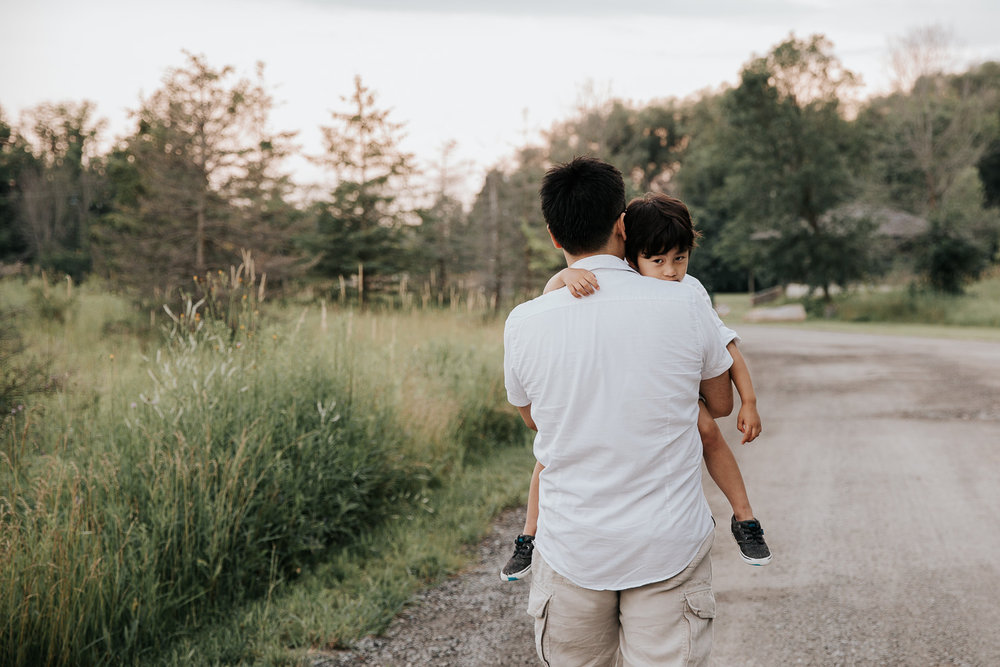 3 year old boy with dark hair looking over father's shoulder at camera as dad carries him down scenic gravel road - Newmarket Lifestyle Photography