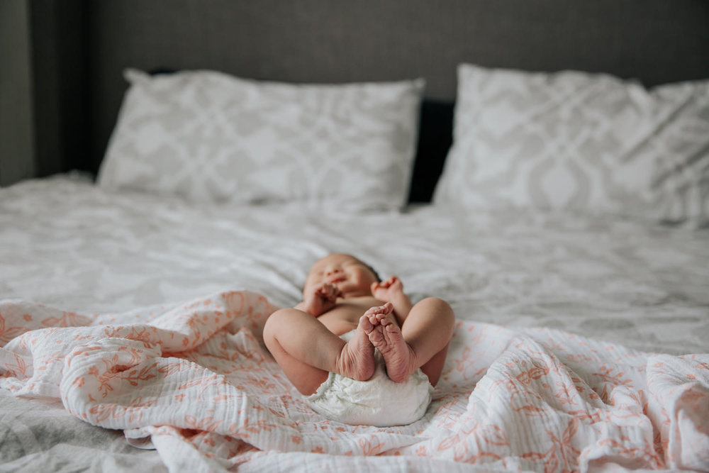 2 week old baby girl in diaper on bed with pink and white floral swaddle, shot of feet tucked up near her body - Barrie Lifestyle Photography