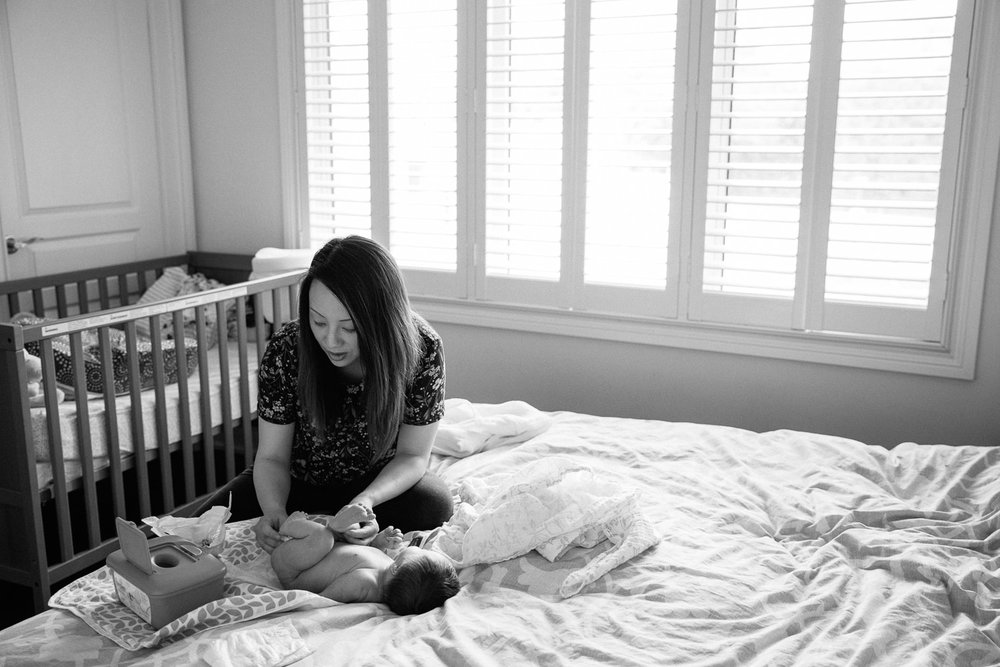 mom with long dark hair sitting on edge of master bed changing 2 week old baby girl's diaper - Newmarket In-Home Photos