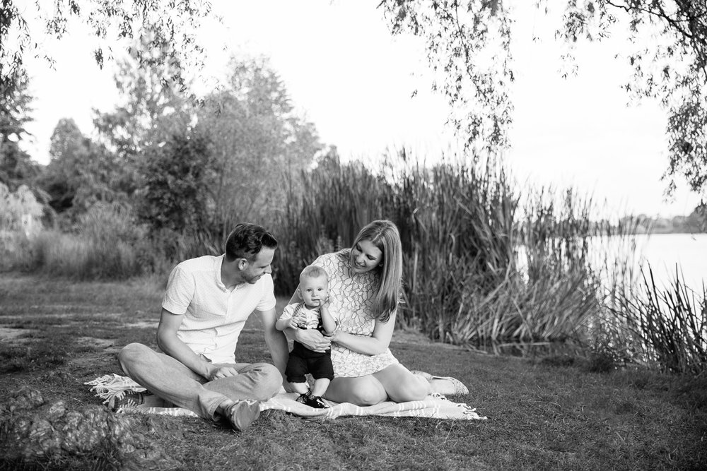 family of 3 sitting on blanket under large willow tree next to pond at high park, 8 month old baby boy standing between mom and dad looking at camera - Stouffville Lifestyle Photography
