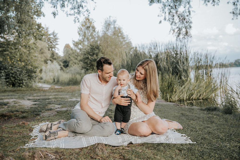 family of 3 sitting on blanket under large willow tree next to pond at high park, 8 month old baby boy standing between mom and dad looking at camera - Markham Lifestyle Photography