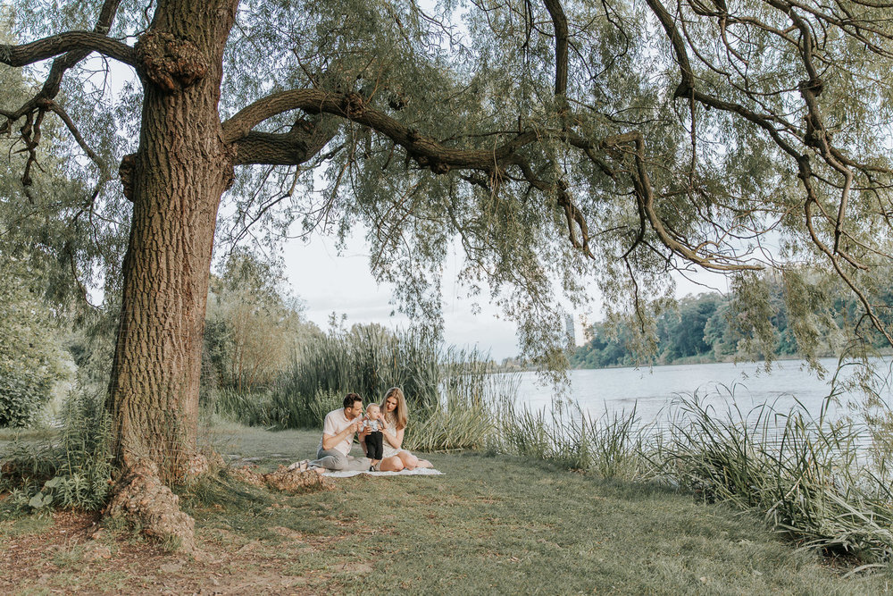 family of 3 sitting on blanket under large willow tree next to pond at high park, 8 month old baby boy standing between mom and dad - Newmarket Lifestyle Photography