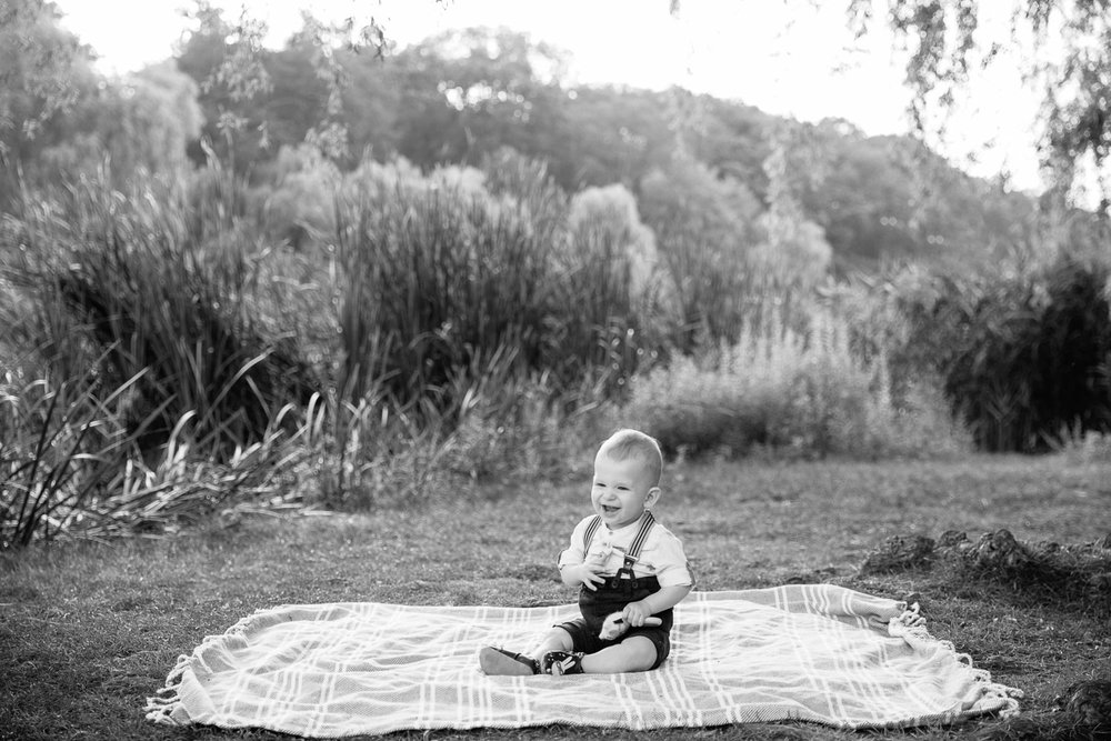 8 month old baby boy sitting on blanket on grass at high park wearing suspenders and button down shirt, holding toy and laughing - Markham In-Home Photography