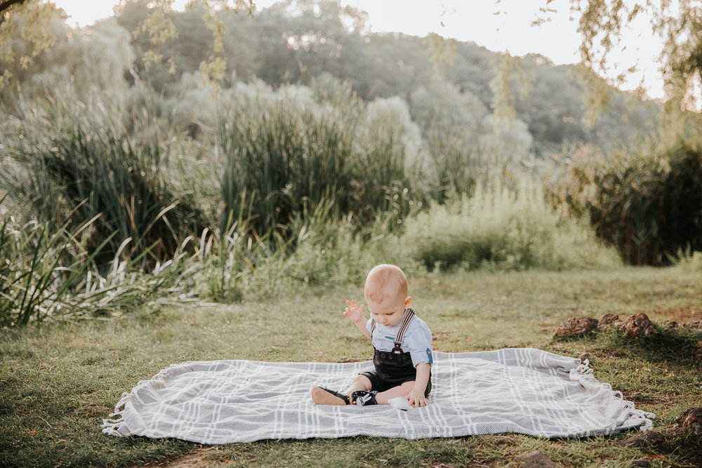 8 month old baby boy sitting on blanket on grass at high park wearing suspenders and button down shirt, looking down playing with toy - Stouffville In-Home Photography