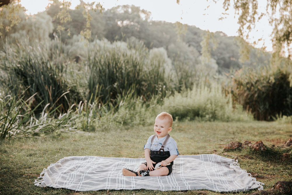 8 month old baby boy sitting on blanket on grass at high park wearing suspenders and button down shirt, holding toy and smiling - Barrie In-Home Photography