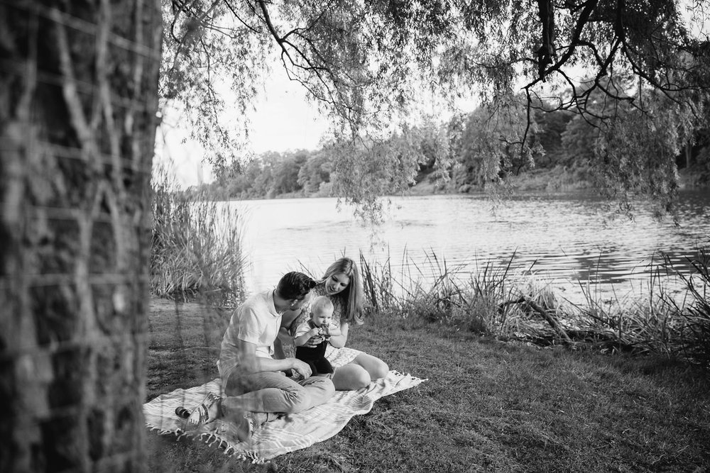 family of 3 sitting on blanket under large willow tree next to pond at high park, 8 month old baby boy standing between mom and dad - Newmarket In-Home Photography