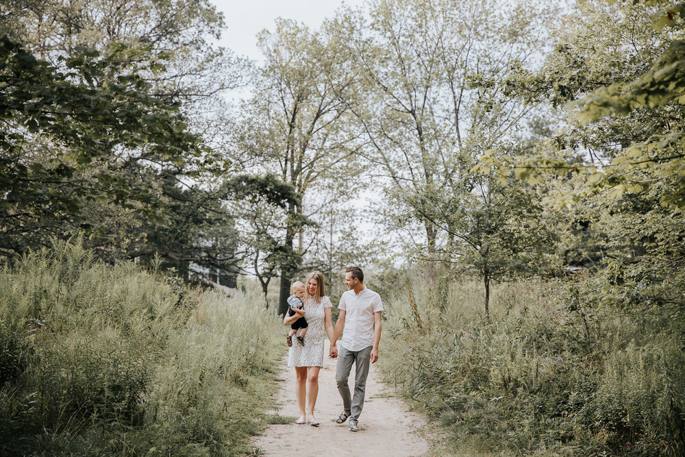 family of 3 walking down dirt path at high park surrounded by tall grasses and trees, mom carrying 8 month old blonde baby boy and parents holding hands - GTA In-Home Photography